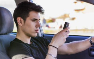 Inattentive Handsome Young Man Busy with his Mobile Phone While Driving a Car.
